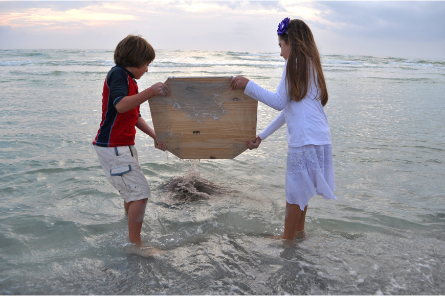 Gabriel and Ella Mirman dump the mixed sand into the Gulf of Mexico at the end of the ceremony.