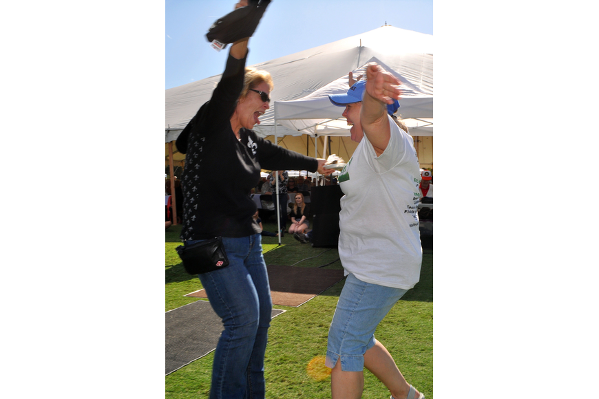 Jo Ann Mixon and Sandi Henley jump for joy and go to hug one another after winning the big raffle prize of $20,000.