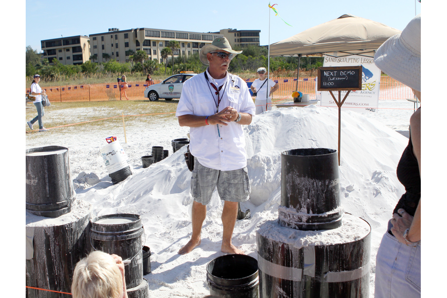 Bill Knight talks to a grouping of people who showed up for a sand sculpting demo during the Siesta Key Crystal Classic.