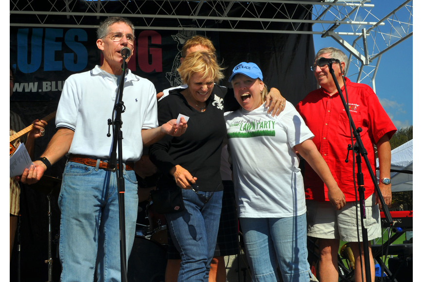 Matt Walsh and John Wild stand on stage with two of the four owners of the winning $20,000 ticket, Jo Ann Mixon and Sandi Henley, Saturday, Nov. 17, at the Longboat Key Gourmet Lawn Party.