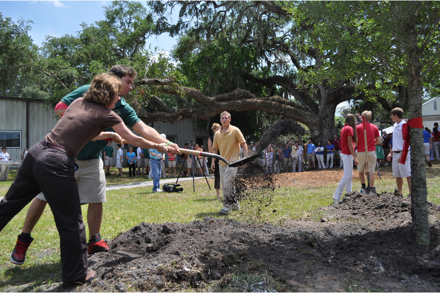 Diane Buhler and George Wall cover the roots of the newly planted tree with dirt.