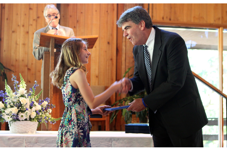 Caitlin Camire shakes hands with Headmaster Mahler while receiving the Academic Award Friday, June 3 during ODA's 6th grade graduation at Siesta Key Chapel.