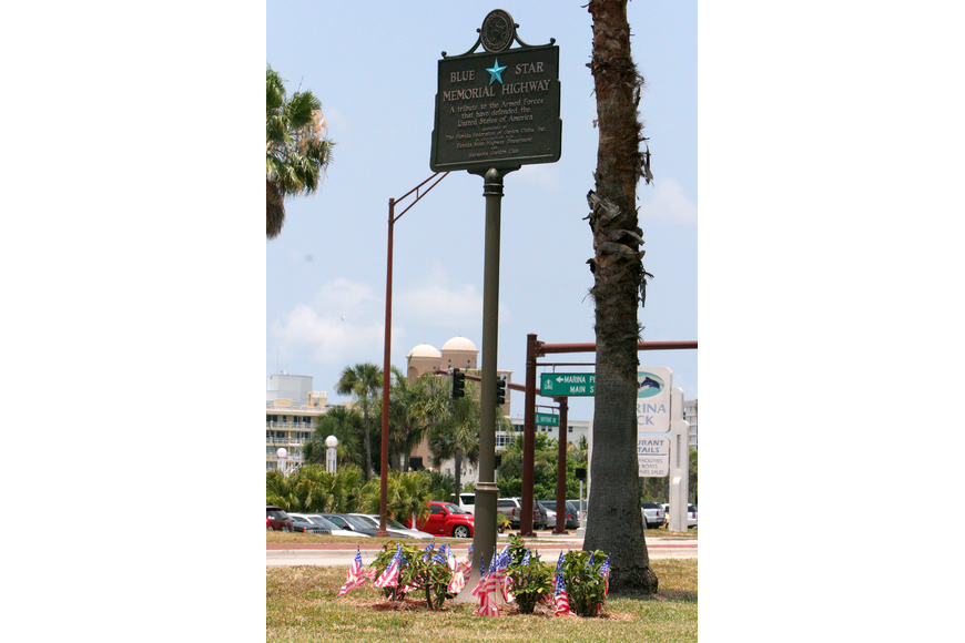 Small, plastic American flags surround the bottom of the sign for the Blue Star Memorial Highway on Tuesday, June 14 in J.D. Hamel Park along Tamiami Trail. In the United States, Flag Day is celebrated on June 14.