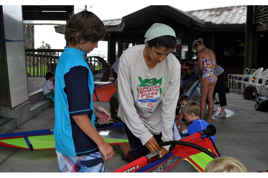 Ariana Abid helps Nick Burback, 12, put together one of the wind surfing sails during a learning exercise Friday, July 8 during the Island Style Water Sports Camp.