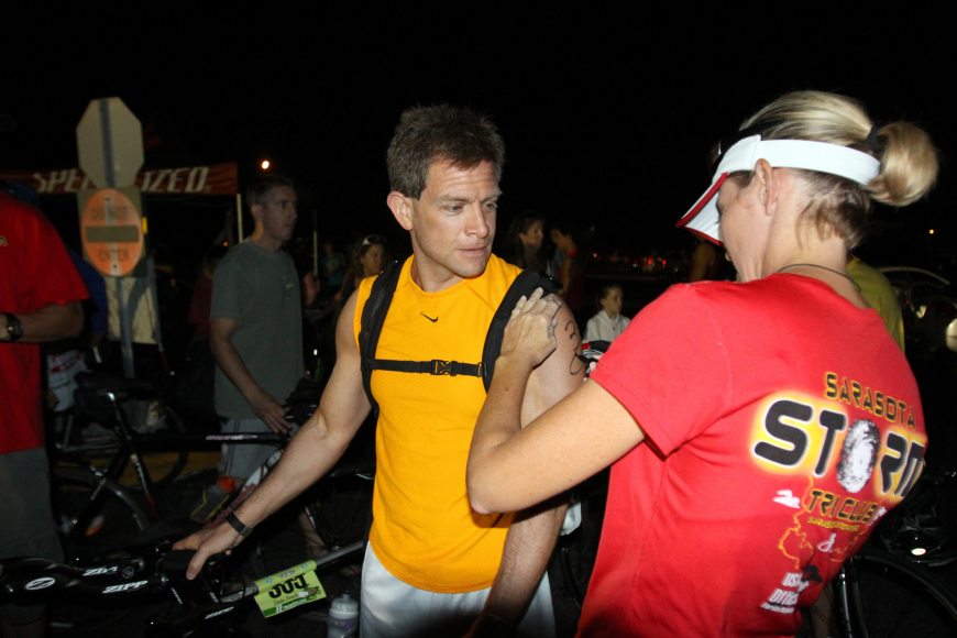 Steve Torres gets marked with his race number, 305, by Nicole Chapman early Saturday morning prior to the Siesta Key Triathlon.