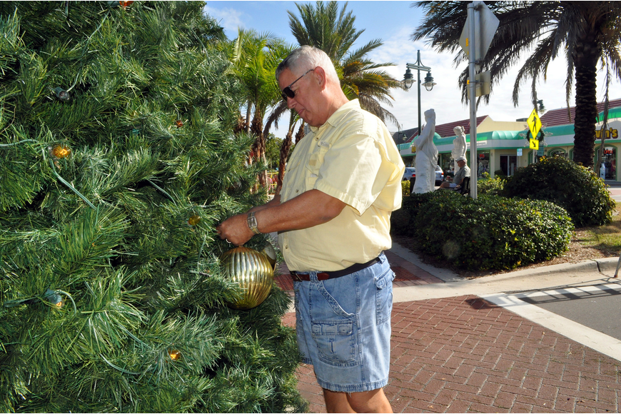 Bill Carman hangs a gold ball onto one of the tree limbs during the tree decorating, Saturday, Nov. 19, out on the circle.