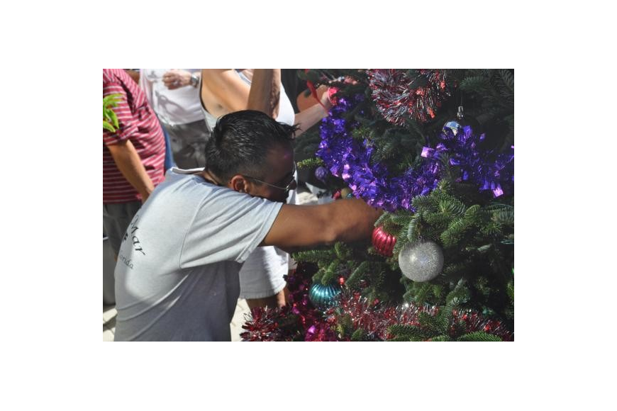 Elton Arellano decorates the Casa Del Mar Christmas tree. Photo by Mallory Gnaegy.