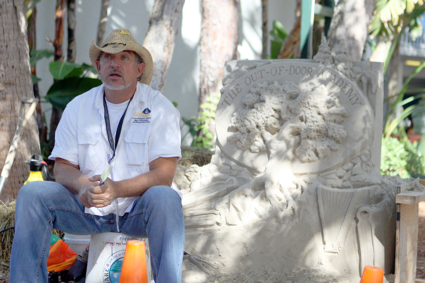 Brian Wigelsworth with his sand sculpture of ODA's logo.