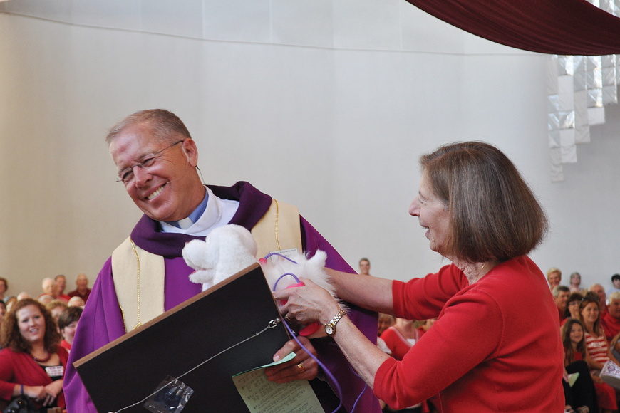 The Rev. Don Henry receives gifts from Sister Judy Baldino in March at a celebration honoring Henry's 10th year as priest of St. Thomas More Catholic Church and his 40th year as a priest.