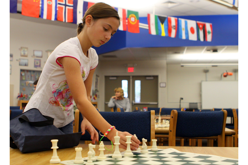 Brooke Witte helps to set up the chessboards before the Tournament of Hearts, Saturday, Feb. 11, in the library at Phillippi Shores Elementary.
