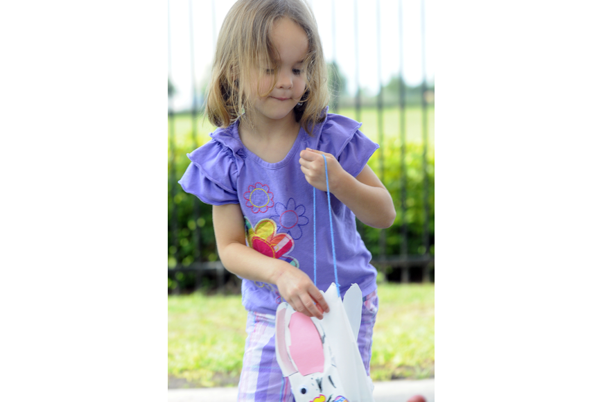 Natalia Chadbourne, 4, carefully places another egg in her Easter Bunny bag.