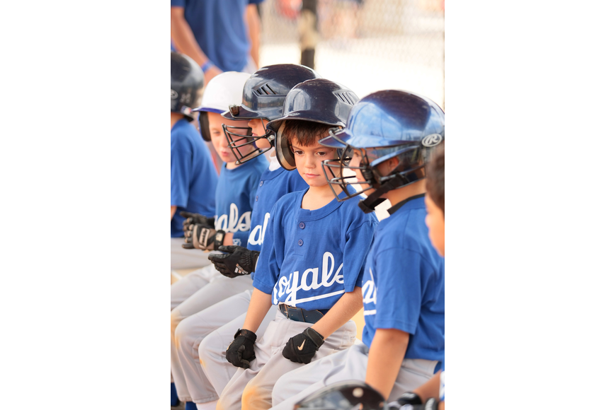 Jackson Watrobsky and his Royals teammates wait in the dugout for their turn to bat.