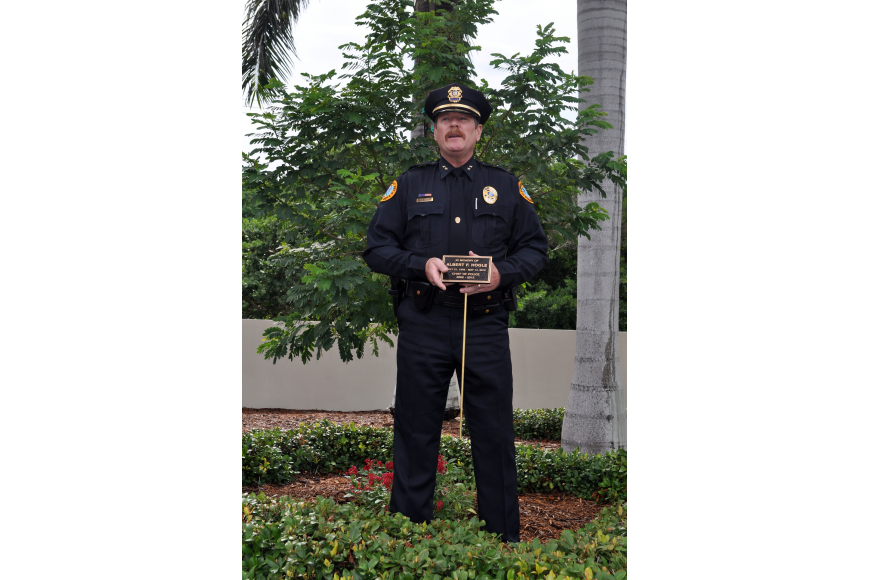 Longboat Key Police Chief Peter Cumming holding the plaque that will place in front of the tree that was planted in honor of Al Hogle Wednesday, Oct. 3 at the Longboat Key Police Station.