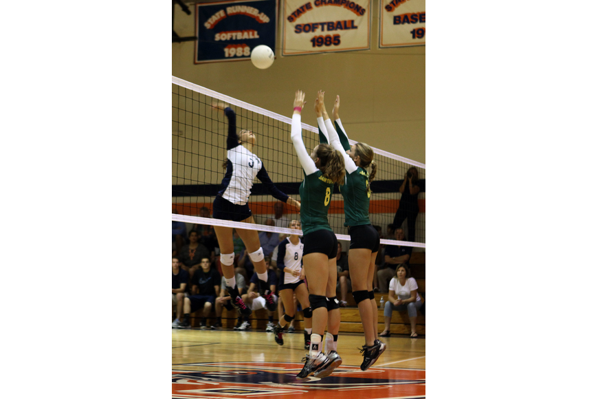 Gabriella Costa, No. 3, goes up to spike the ball at Tori Biach, No. 8, and Talia Barker, No. 3.