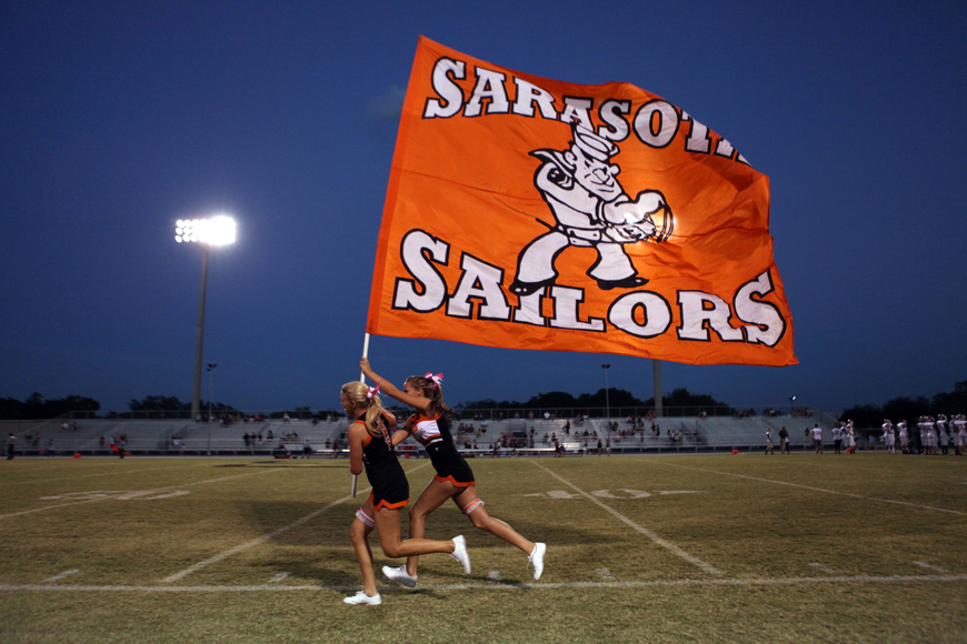 Sailor cheerleaders run up and down the field with a large Sarasota Sailors flag before the game.