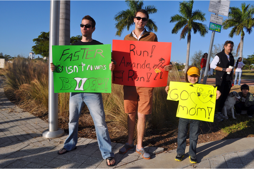 Alex Alston, Steven Piskoty and Daniel Desear, 5, hold up signs to cheer on Amanda Desear during the 2nd Annual Achieva Reindeer Trot Saturday, Dec. 1, at Payne Park.