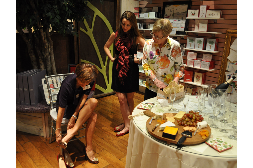 Patti Eisemann tries on shoes as Diana Kelly and Ann Leibel watch.