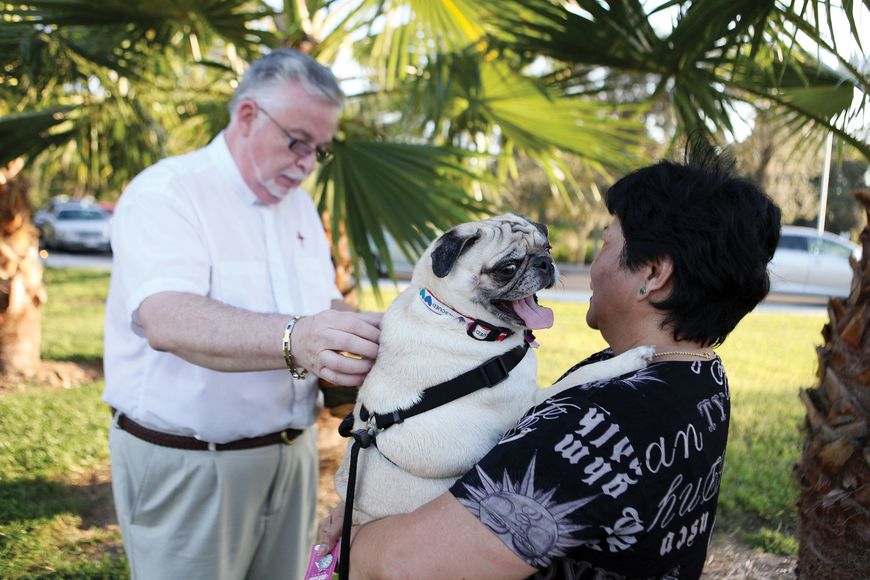 Deacon Tom Grant blesses Mary Seguerra's dog, Pugley, 2, at Our Lady of Mount Carmel's pet blessing.