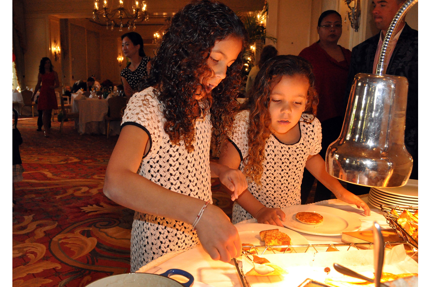 Amber Baylis, 9, and her sister Ava, 6, pick out which pancakes and pieces of French toast they want for breakfast Sunday, Dec. 16, at the Breakfast with Santa event at the Ritz Carlton.