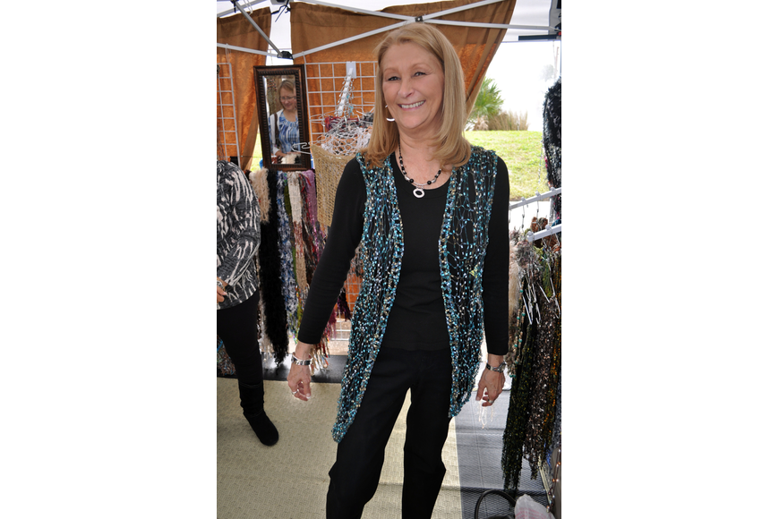 Debbie Alden tries on a vest made by Daniela Viteri.