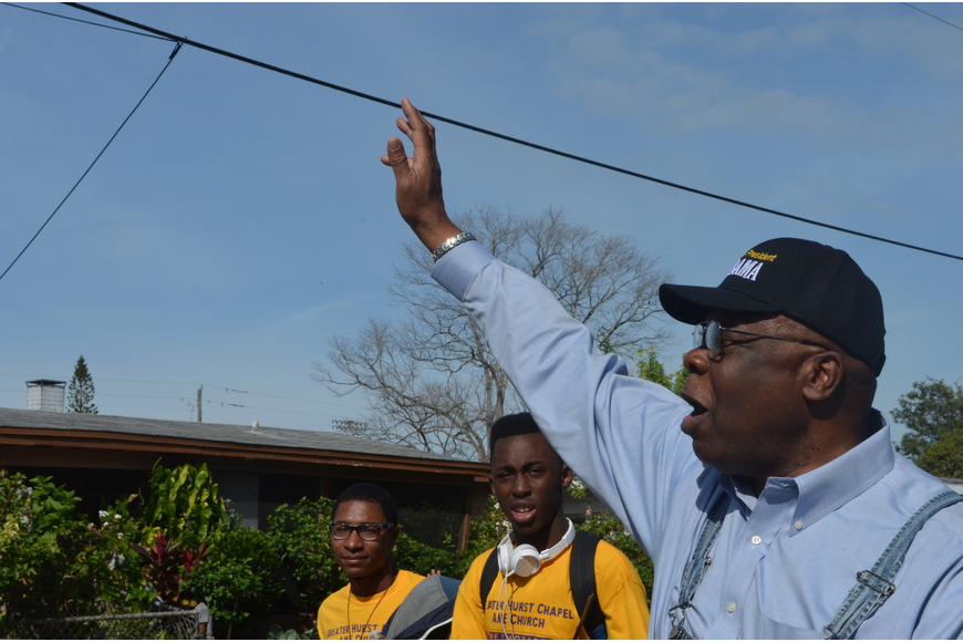 Vice Mayor Willie Charles waves hello to neighbors as he marches with community members.