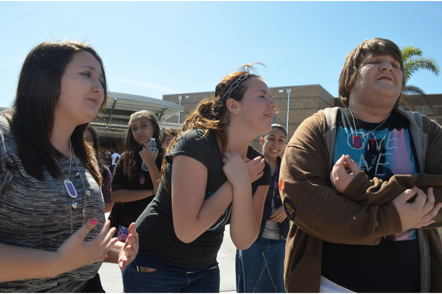 Sophomores Alexis Rutter, Rachel Rohn, and Brandon Thomas sing along to a pop song during the rally.
