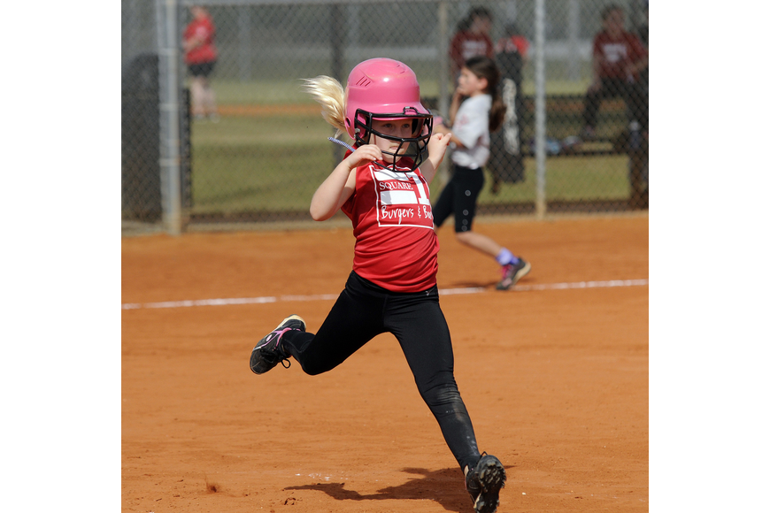 Seven-year-old Erin McIntyre races down to first base.