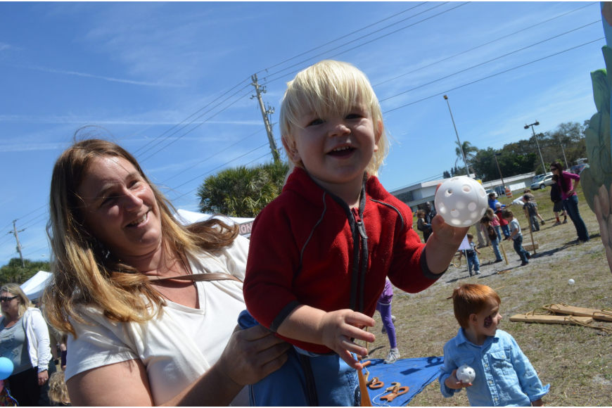 Heidi Dahlborg holds her son Toby, 2, as he throws a ball in Pinocchio's Land.