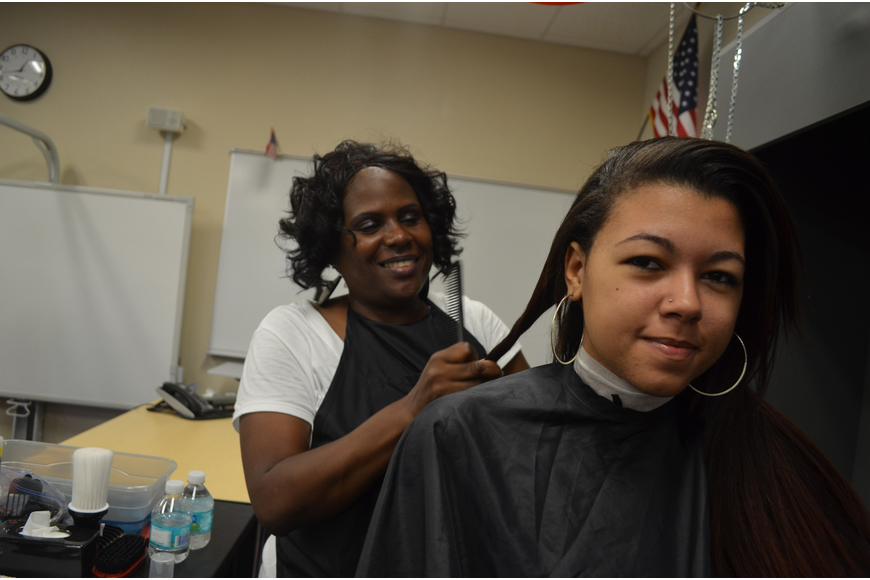 Shalonda Robinson of Smart Style volunteers her time and does 17-year old Alexis Bowers's hair.