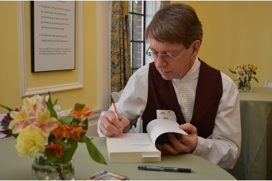 Rick Smith personalizes books for the guests.