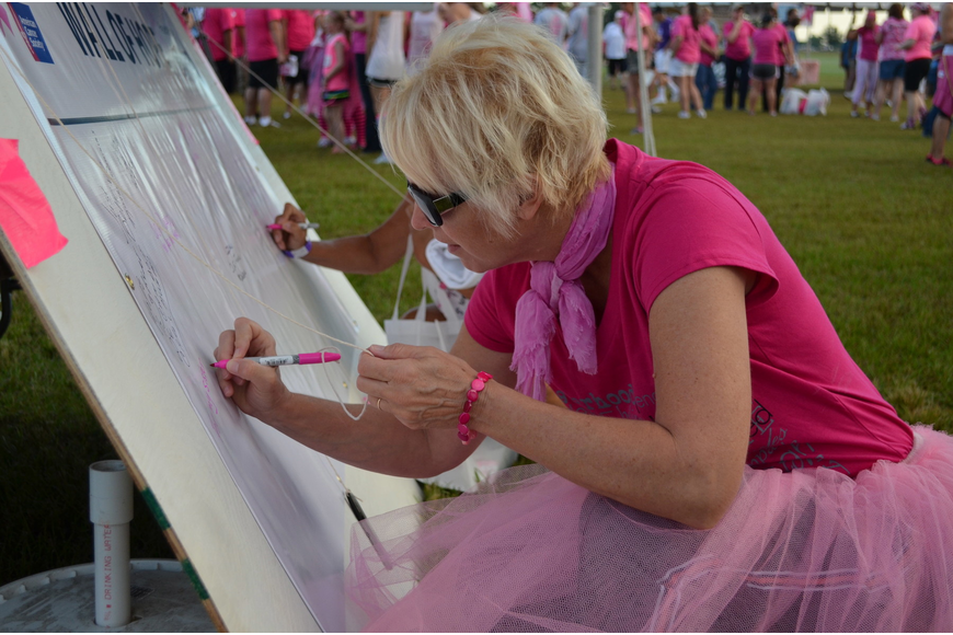 Deb Van Schoick writes a message on the Wall of Hope.