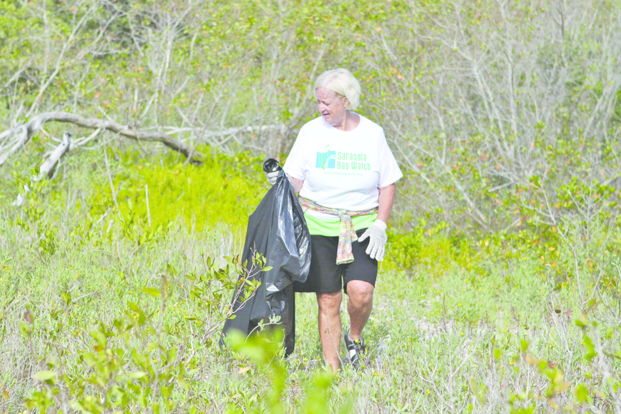Betsy Falls searches for trash May 11 at the fifth annual Sarasota Bay Watch Sister Keys Cleanup. Volunteers collected a ton of trash. 3