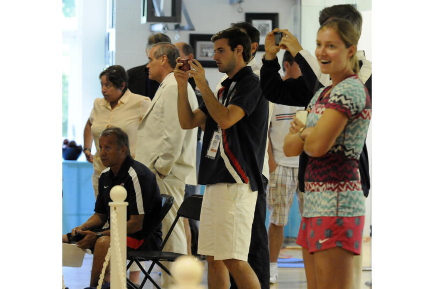 Members of the United States coaching staff and spectators cheer on the team during its bout with Belarus.