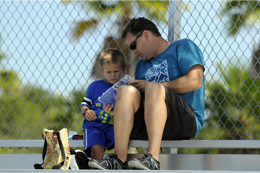 Steve Butler looks over the program with his 3-year-old son Lance. The two planned to attend all five mixed relay events June 8, and were especially looking forward to the laser pistol shooting.
