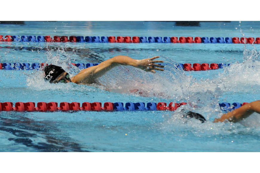 The United States' Nathan Schrimsher takes a lead heading into the final turn of the 200-meter freestyle mixed relay.