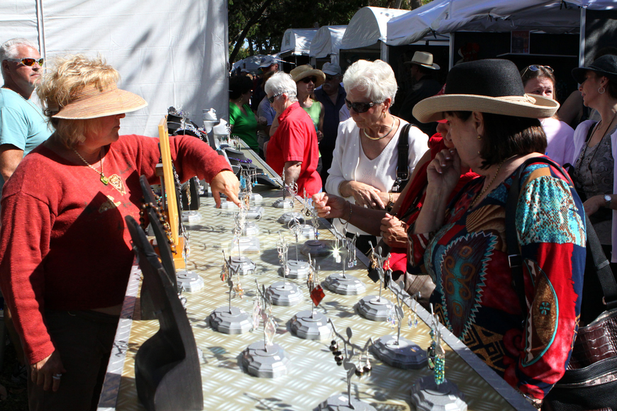 People attending the art festival look at the jewelry created by Florida Fusion.