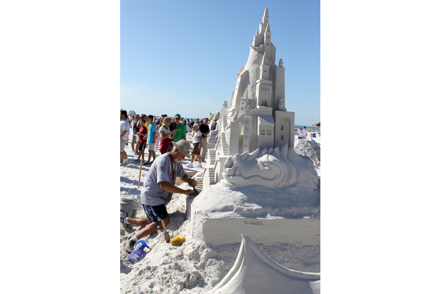Ky Terrell works on the sand sculpture he and Andy Hancock created entitled