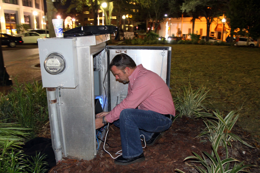 Matt Gregg works on fixing a few last minute things before the 7 p.m. inaugural display of Five Points Selby Park's new tree light system. Gregg is from Synergy Lighting and was the man who designed and specified the lighting display.