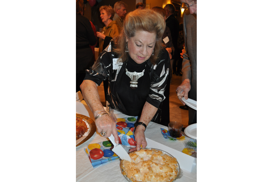 Lois Scheyer cuts a piece of lemon meringue pie made by Hadassah Strobel.