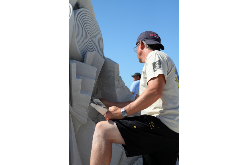 Fred Mallett does some repair work on his sand sculpture.
