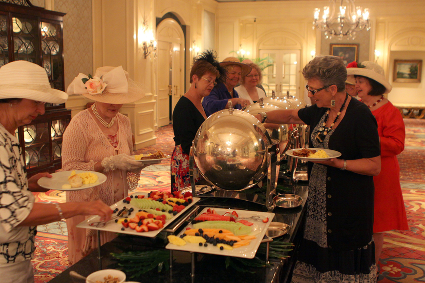 People fill their plates with British food while participating in the royal wedding party Friday, April 29 at the Ritz Carlton.