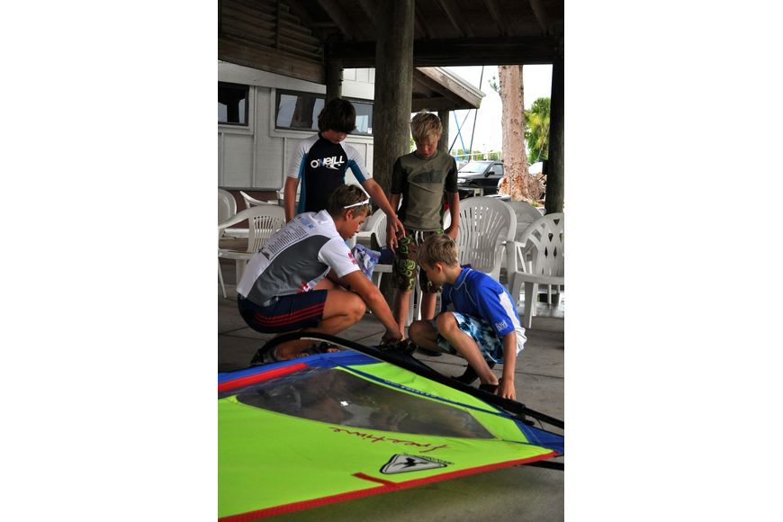 Nick Edwards, 14, a previous week's camper, helps Justin Brush, 11, Chris Van Derzee, 10, and Robbie Van Derzee, 12, during a rigging race Friday, July 8 during the Island Style Water Sports Camp.