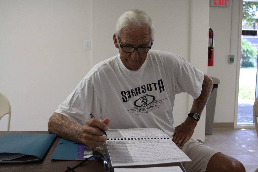 Bob Clousson reads through his manual Saturday, July 30 inside the Turtle Beach Community Center where the seagrass meeting was held.