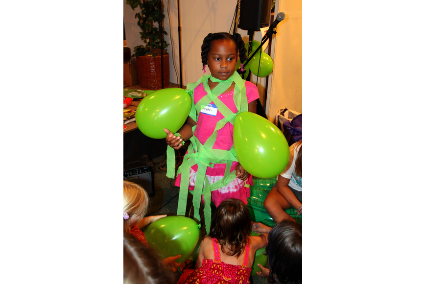 Daysha Brown, 8, gets covered in green crepe paper and balloons during a game Monday, August 8 during vacation bible school at Siesta Key Chapel.