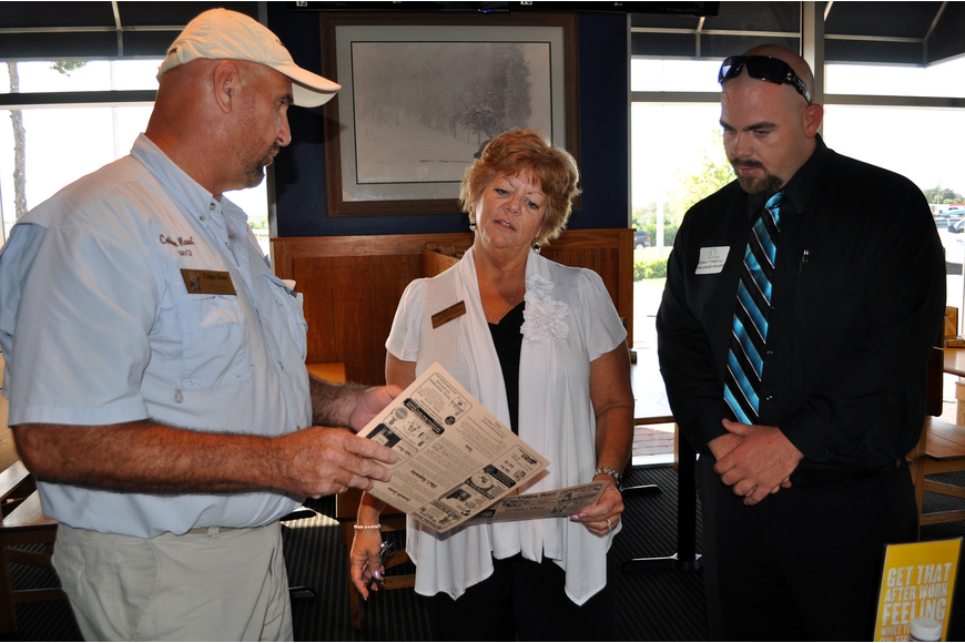 Ed Koehler of Coffee News shows Pat Martin and Shaun Martin of Pampered Movers a copy of Coffee News during the Siesta Key Chamber luncheon Friday, Oct. 7 at Buffalo Wild Wings.