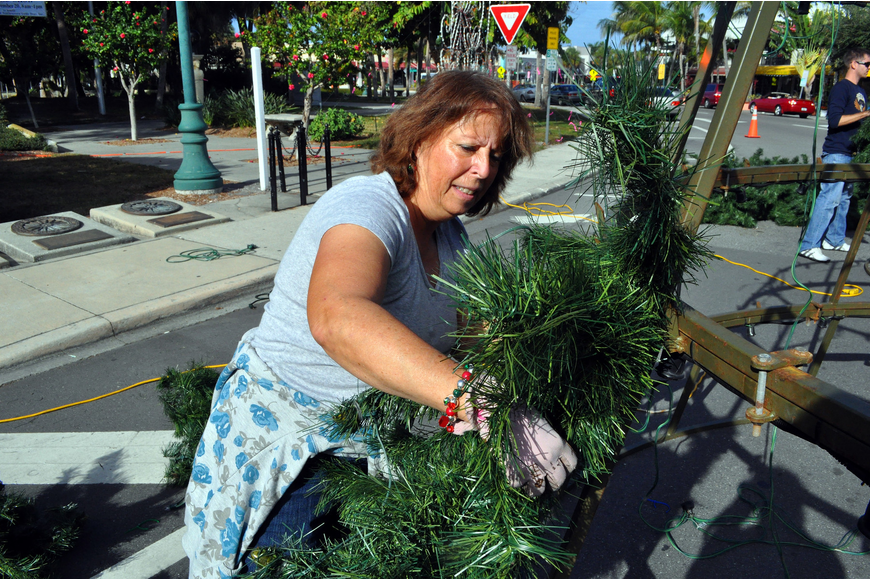 "Joanne Gonet ""fluffs"" a tree branch and puts it on one level of the large tree during the tree decorating, Saturday, Nov. 19, out on the circle."