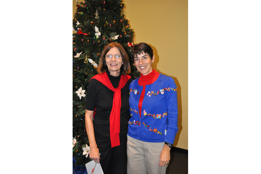 Peg Davant and Betsie Danner pose together by the tree in the Parish Hall.