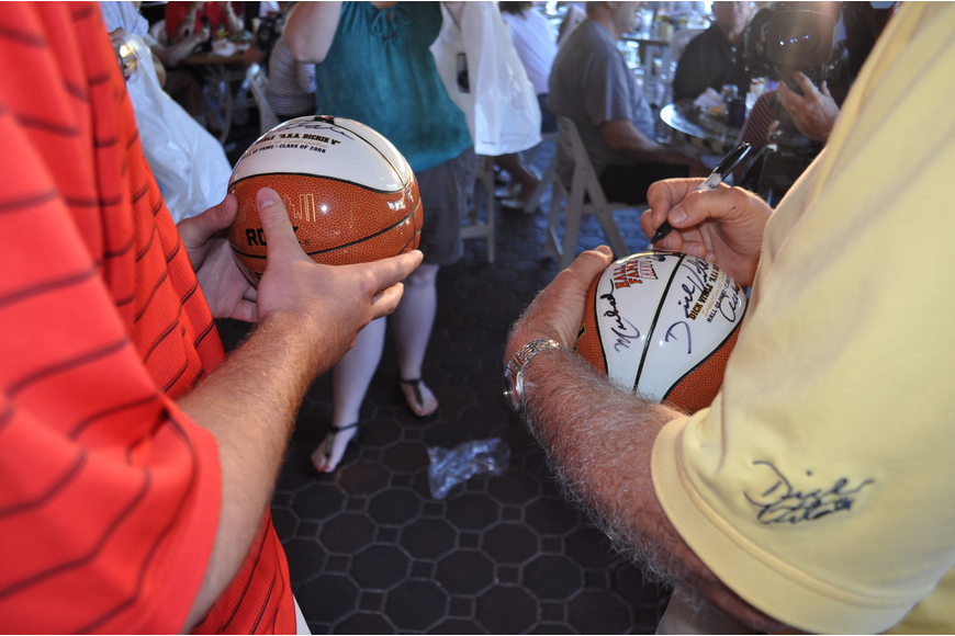 Dick Vitale signs two basketballs for Michael Fear.