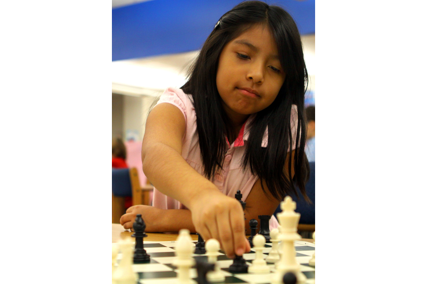 Vanessa Aparicio makes a move during her chess match, Saturday, Feb. 11, in the library at Phillippi Shores Elementary.