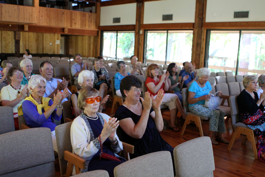 The crowd claps after Dr. Zachary Johnson finishes playing a piece on his guitar, Sunday, March 25, at Siesta Key Chapel.